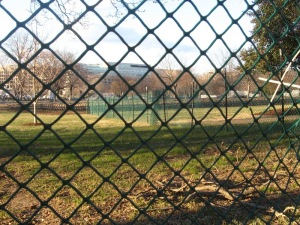 In a park, two levels of wire fencing restrict general access to rows of seats