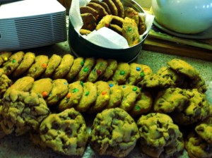 Three columns and a round tin of M&M and chocolate chip cookies.